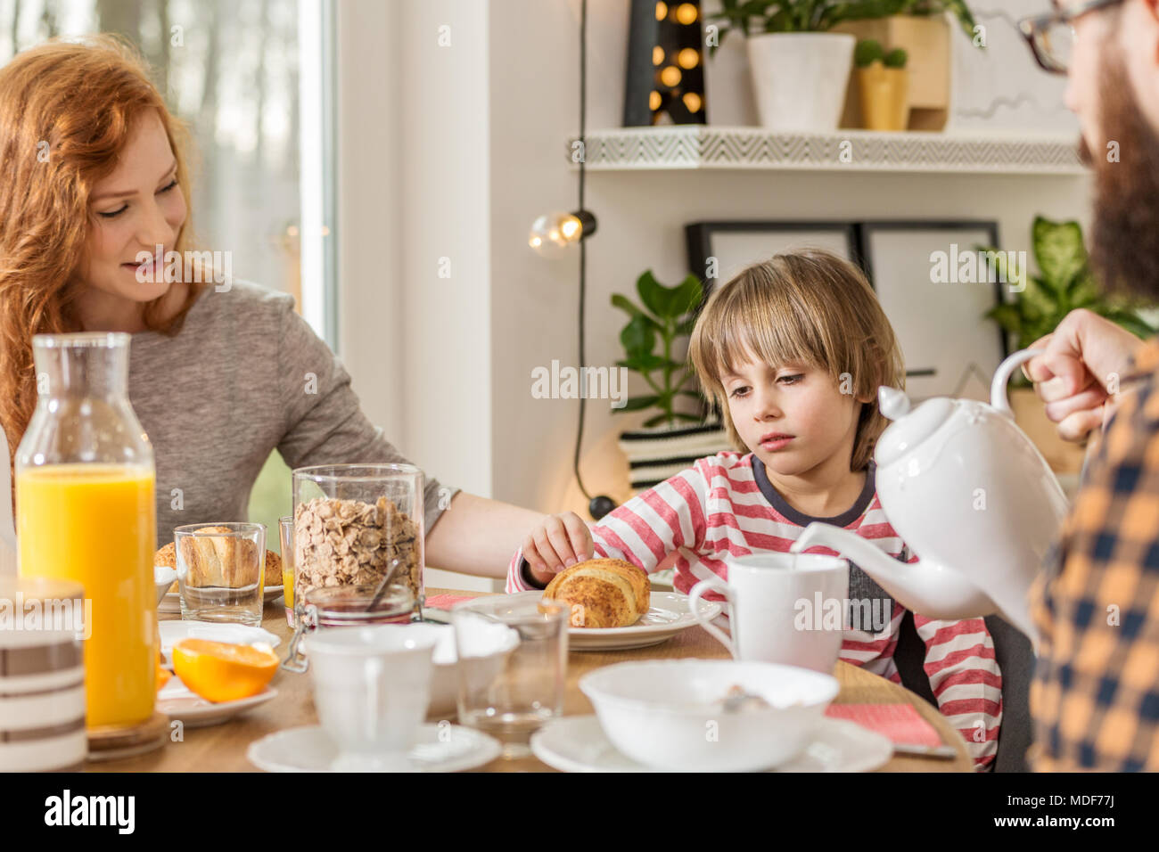 Beautiful mother convincing her son to eat bread for breakfast Stock Photo