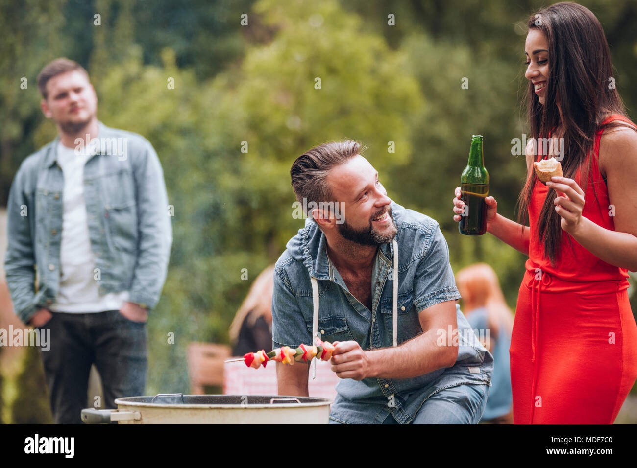 Smiling couple having a barbeque with their friends in the garden - Stock Image