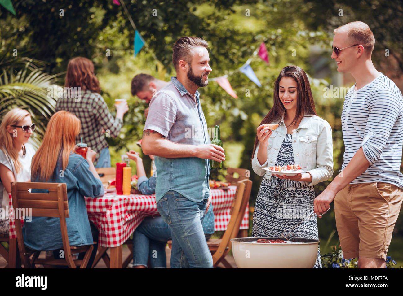 Student friends talking over a grill during a garden party in the summer - Stock Image