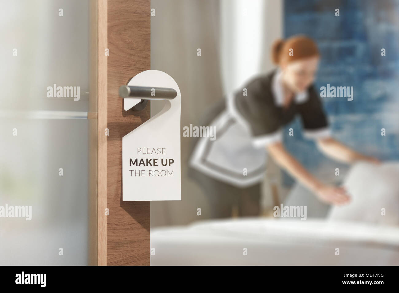 A housemaid cleaning a room in the background and door with a sign at the front Stock Photo