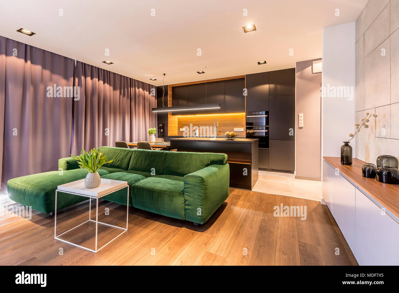 Oak Trendy White Desk Concepts Open space apartment interior with white table near green corner sofa in  front of a black, glossy kitchen with dining table