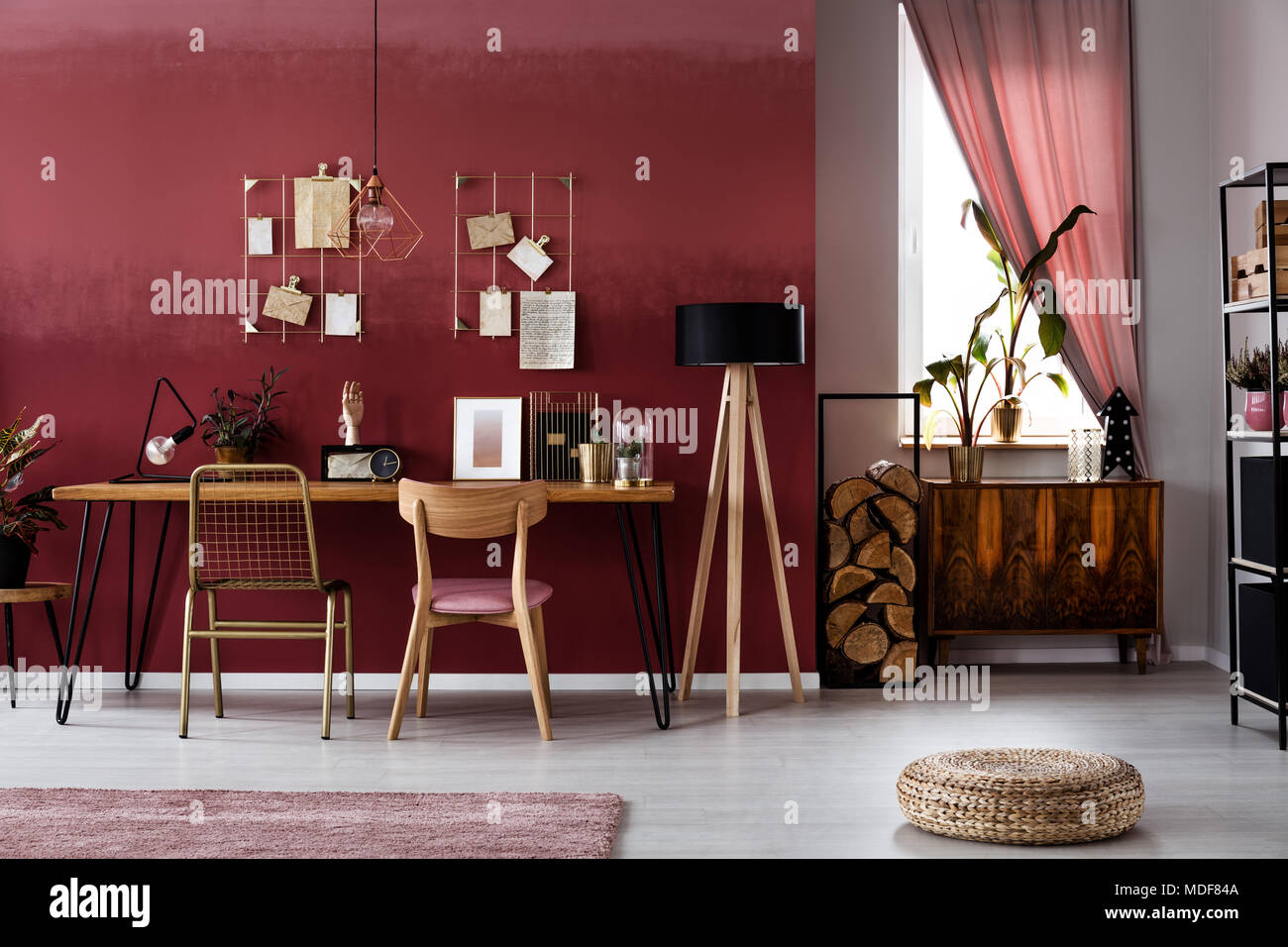 Plant on wooden cupboard against a window in dark red workspace interior with pouf and chair at a table - Stock Image