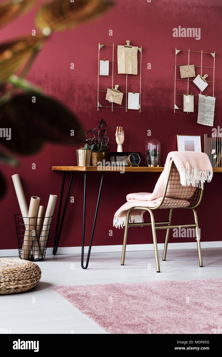 Blanket on gold chair at wooden desk with clock in feminine, pink home office interior - Stock Image