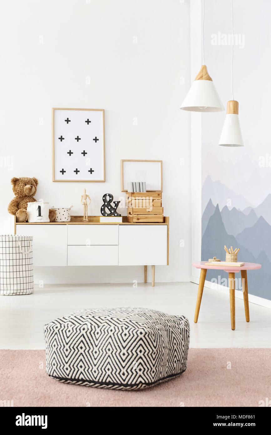 Black And White Pouf With Pattern Placed In Bright Kids Room Interior With  Posters And Decor On Wooden Cupboard