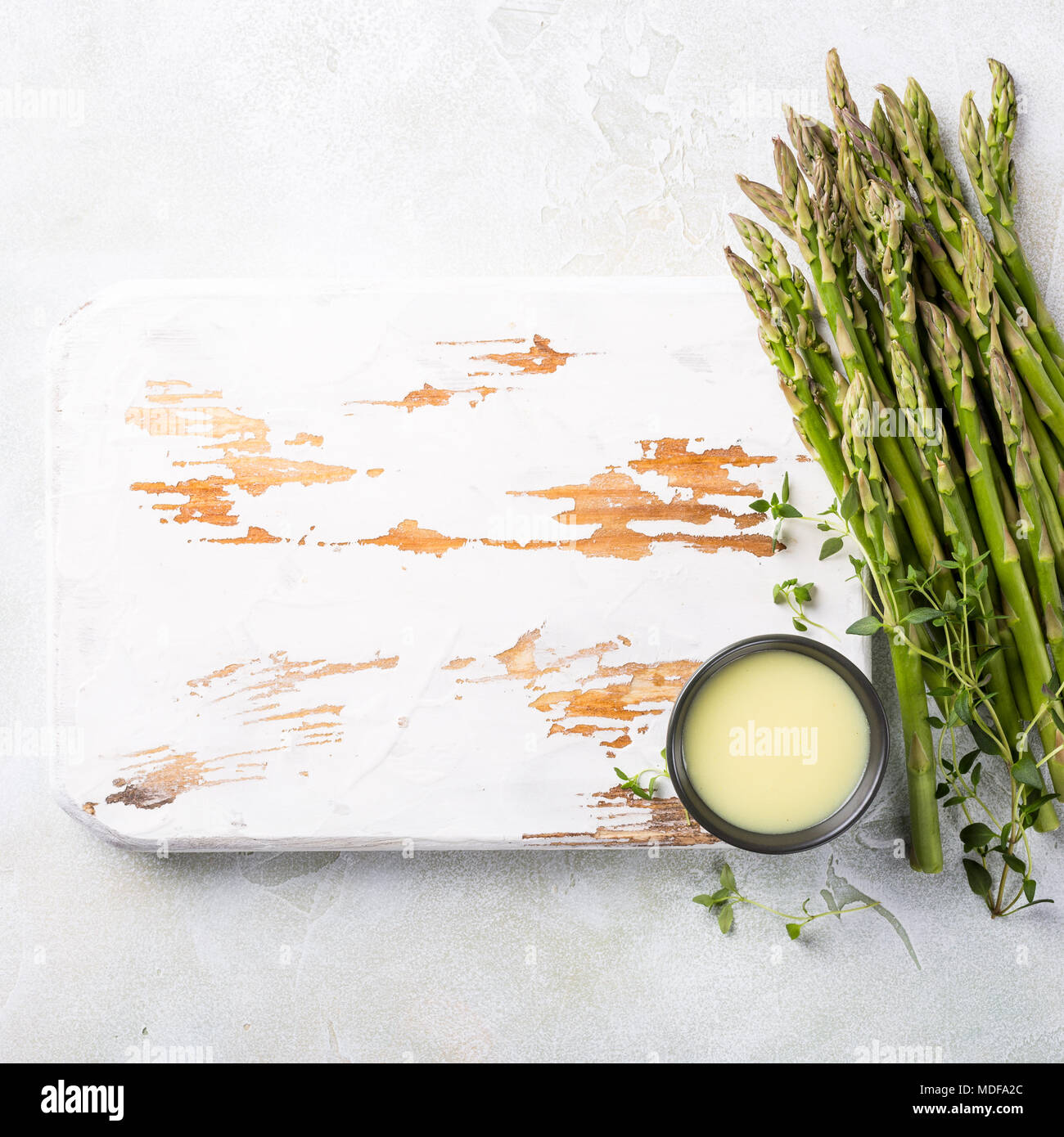 fresh green asparagus and old white wooden board - Stock Image
