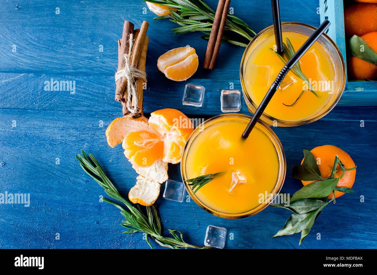 refreshing cocktail with tangerines, juice and ice in glass on a white wooden background, alcoholic drink, copy space Stock Photo