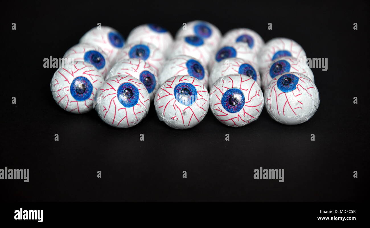 Chocolate candy eyeballs arranged as a background for Halloween. Focus is on the eyeball at the front. Ready to hand out to Trick or Treaters. - Stock Image