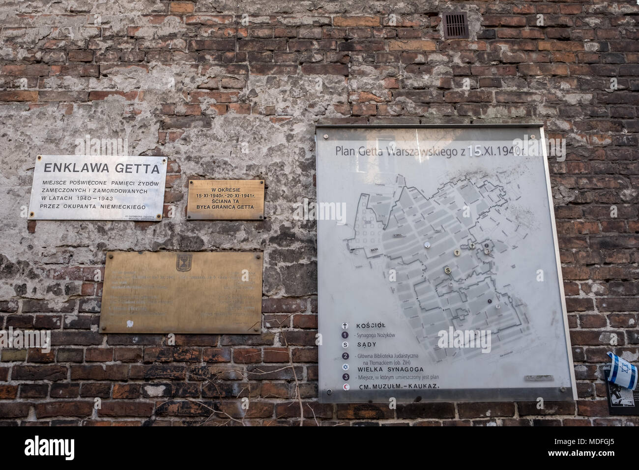 Wall of the historic Jewish Ghetto in Warsaw Poland, showing plaques and map of ghetto on wall. - Stock Image