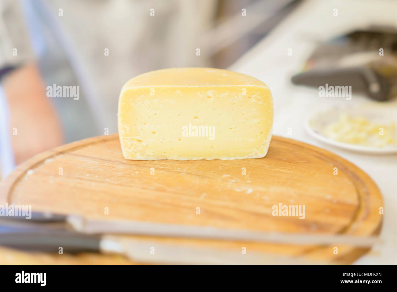 Half cheese head on on wooden market board. Gastronomic dairy produce, real scene in the food market - Stock Image