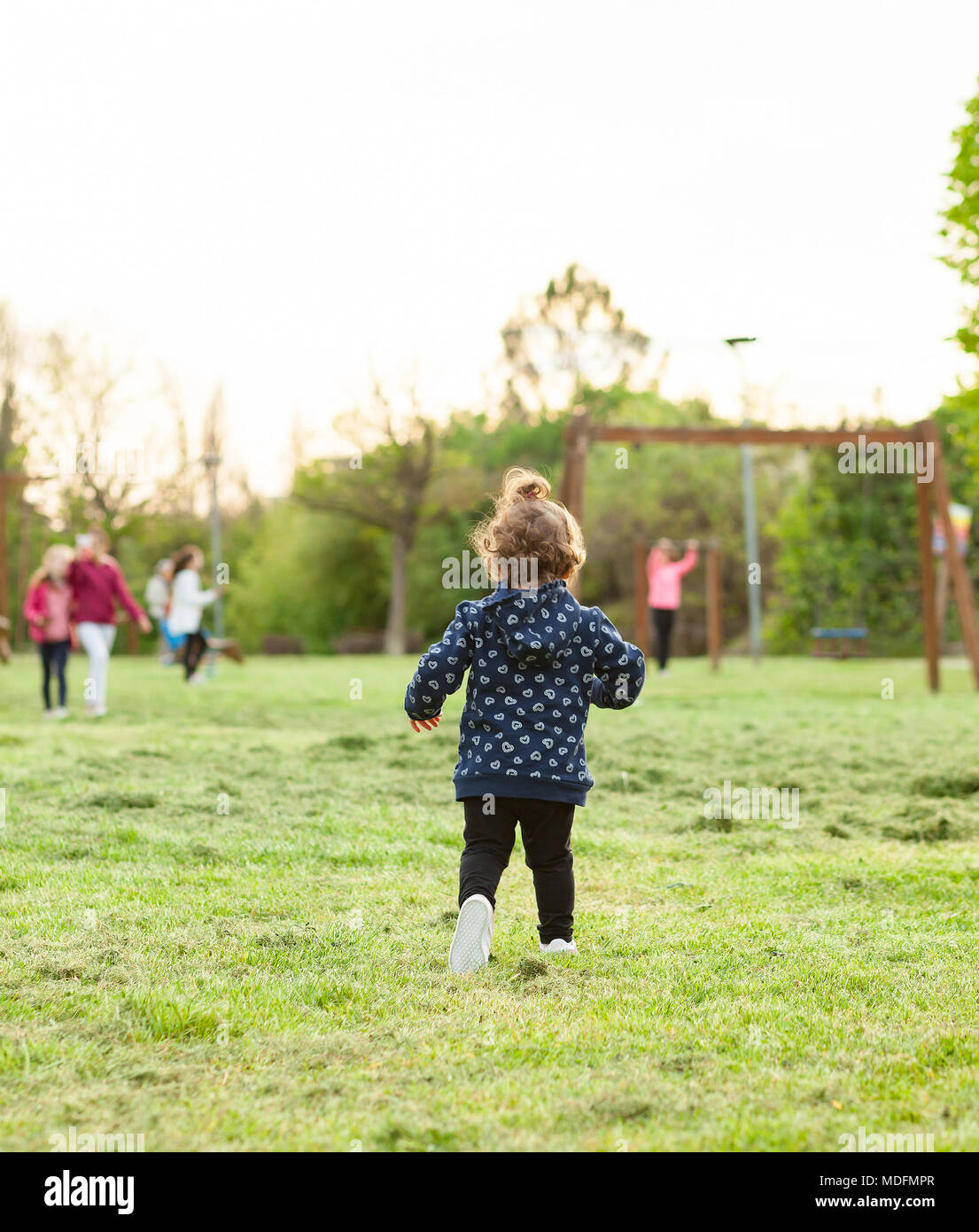 Little girl runs from behind in the park playing with other children. - Stock Image