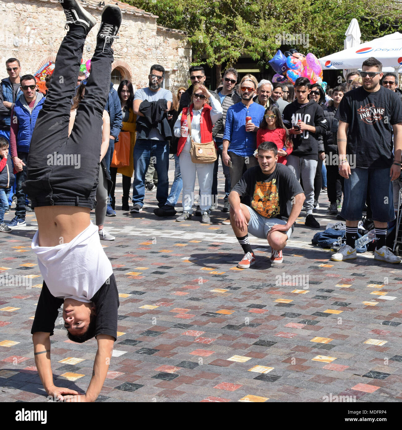 ATHENS, GREECE - APRIL 1, 2018: Man performing breakdance handstand move and crowd of people watching. Street dancing youth culture. - Stock Image