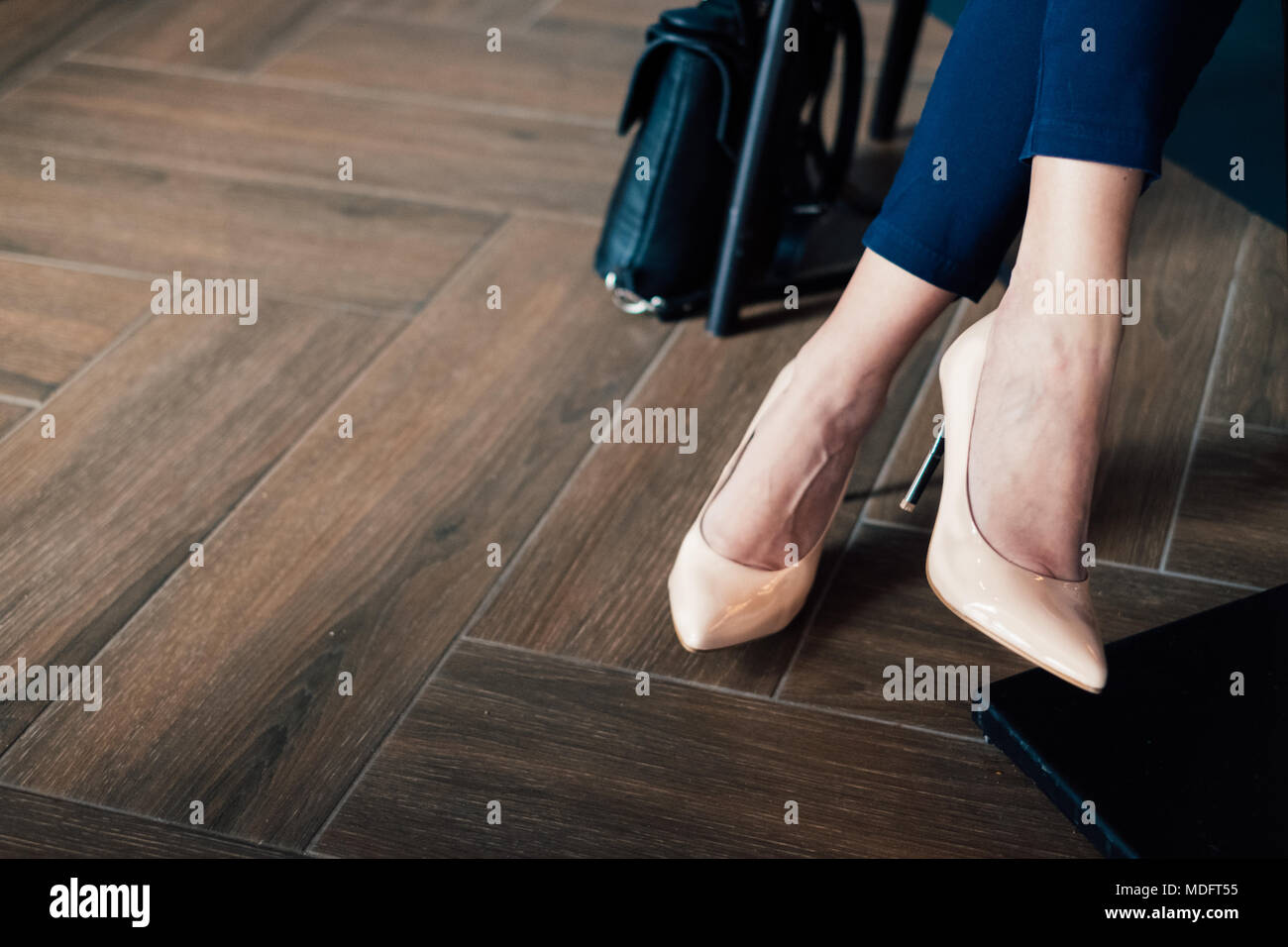 Close-up of a businesswoman's legs in a trouser suit and stiletto heals - Stock Image