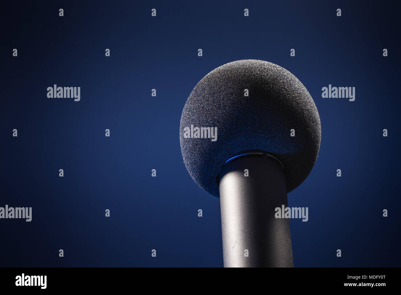 Microphone with black foam ball on a stage - Stock Image