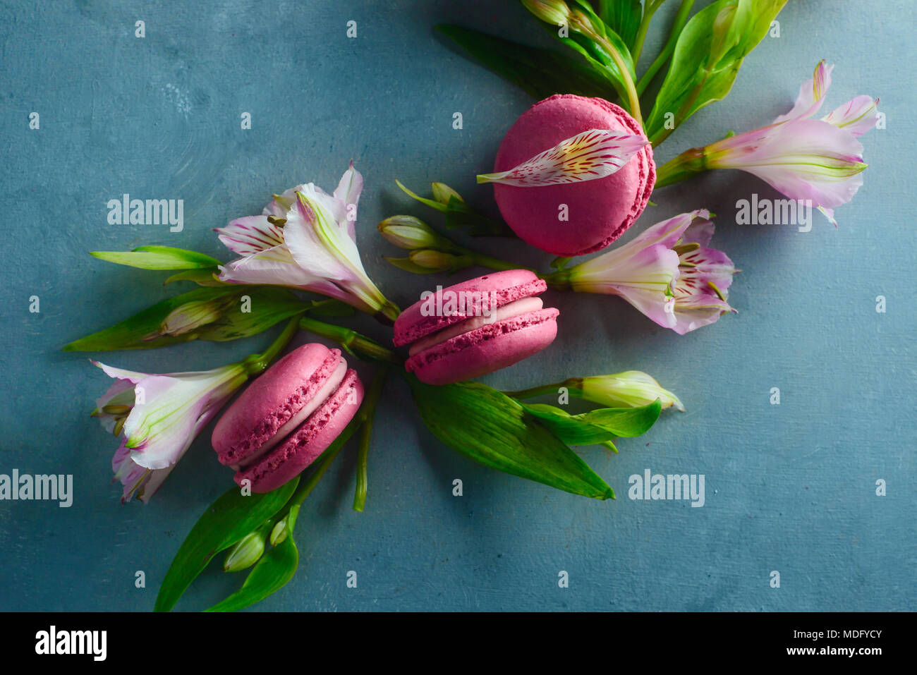 Pink macaroons decorated with pink and white alstroemeria flowers. Romantic French dessert on stone background with copy space. - Stock Image