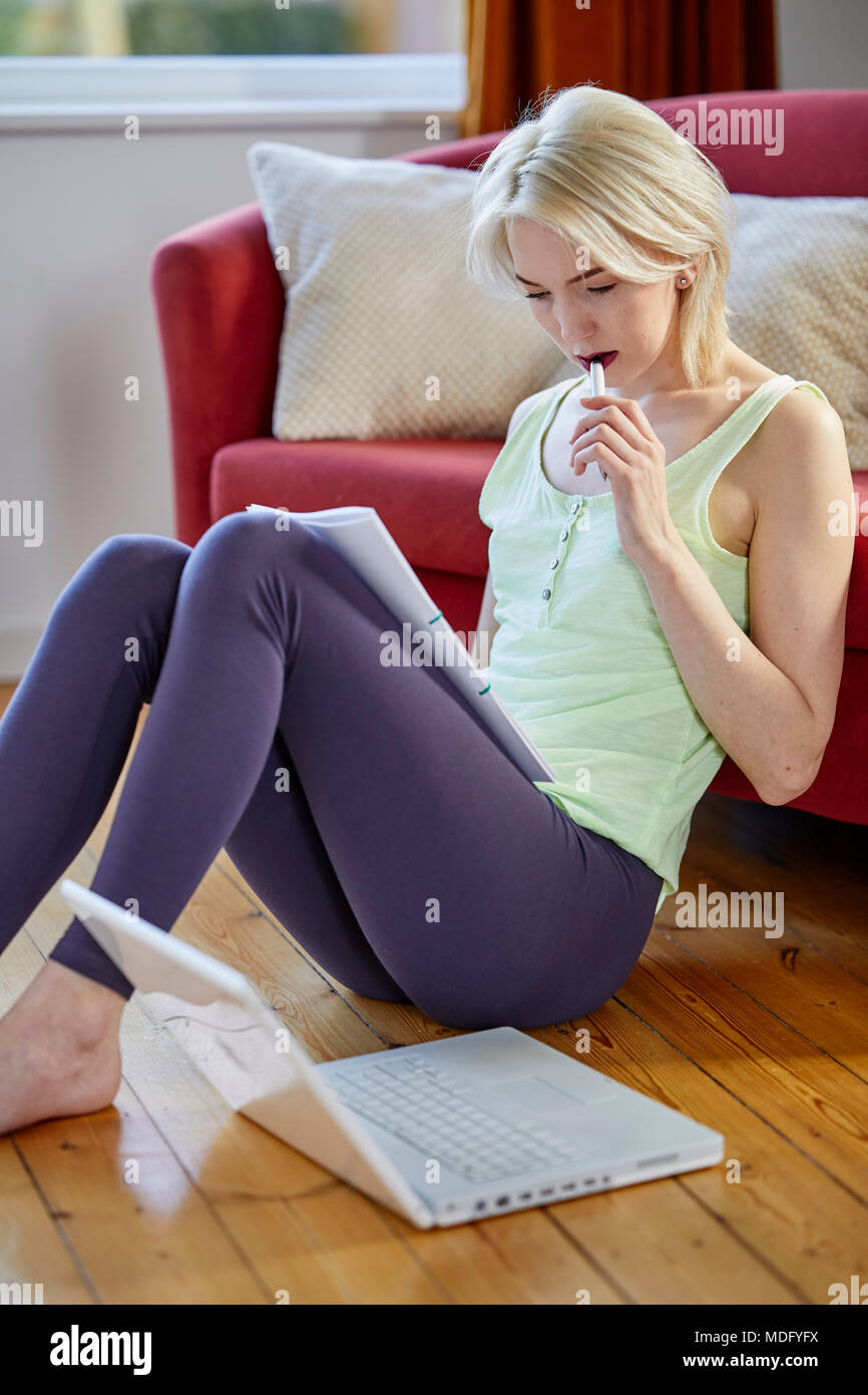Woman sat at home using a laptop computer - Stock Image