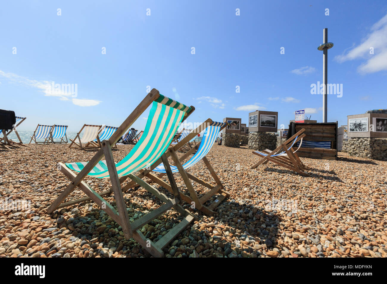 Brighton, United Kingdom - AUGUST 1, 2017: empty striped folding beach chairs on Brighton costline, openair photo exhibition, English channel, British - Stock Image