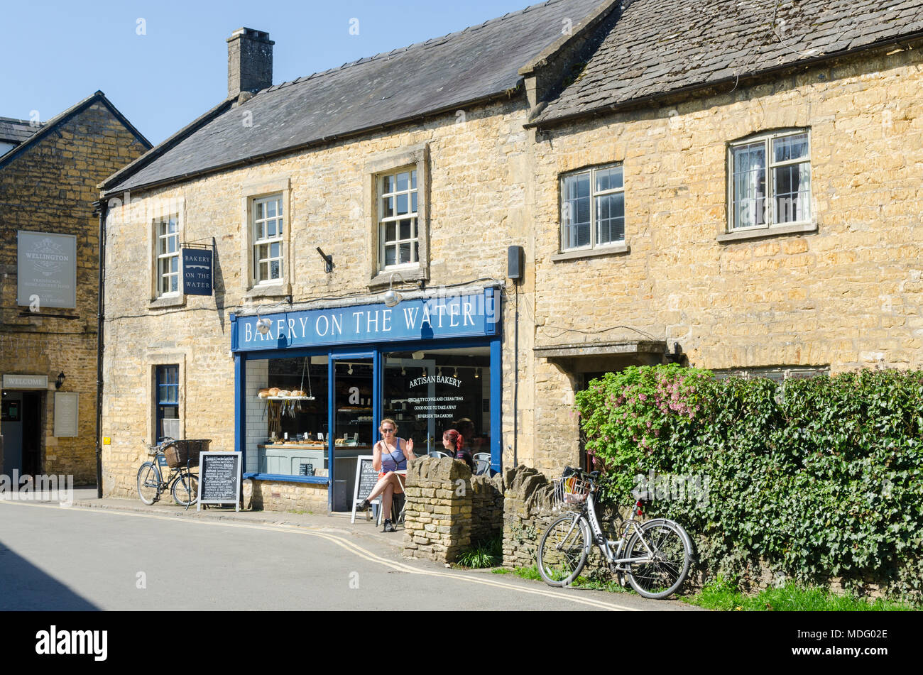 Bakery on the Water artisan bakery in the popular Cotswold village of Bourton-on-the-Water, Gloucestershire in spring sunshine - Stock Image