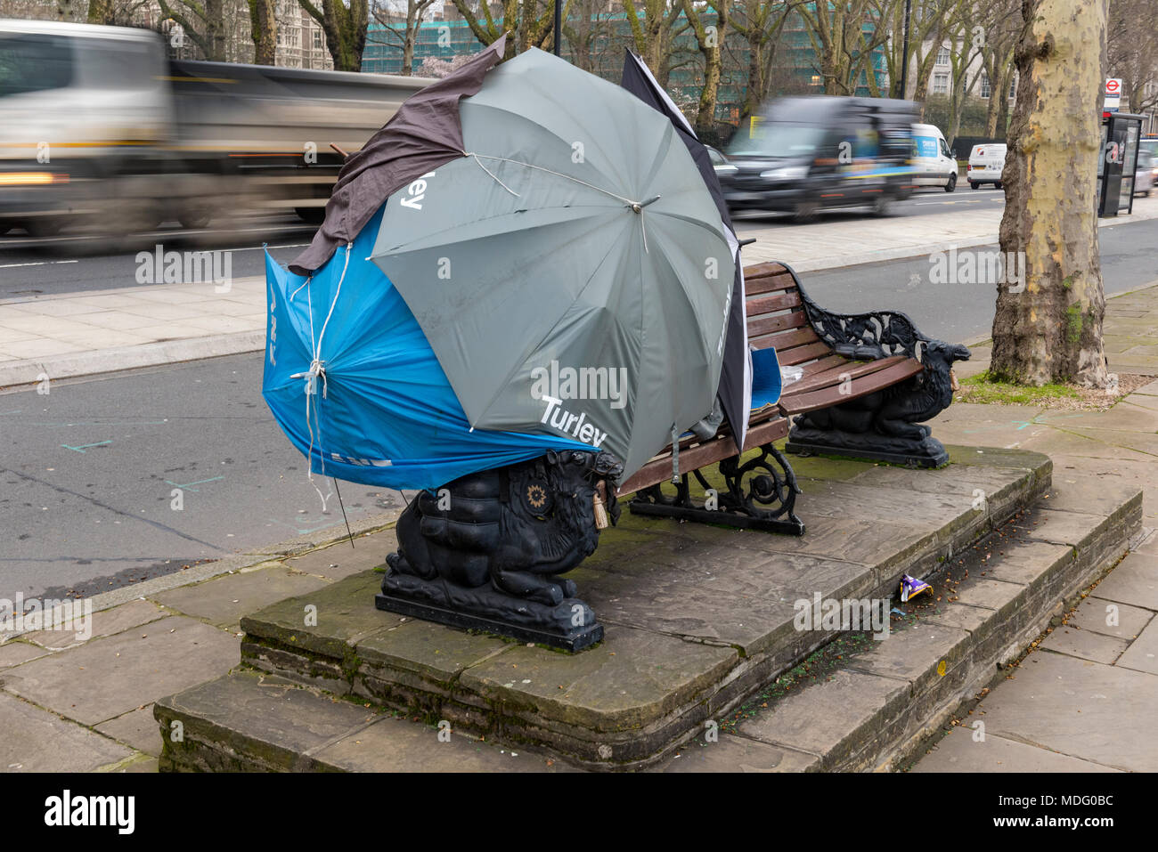 a makeshift shelter for a homeless person on a bench on the north bank of the river thames in central london. umbrellas made into a tent as a shelter. - Stock Image