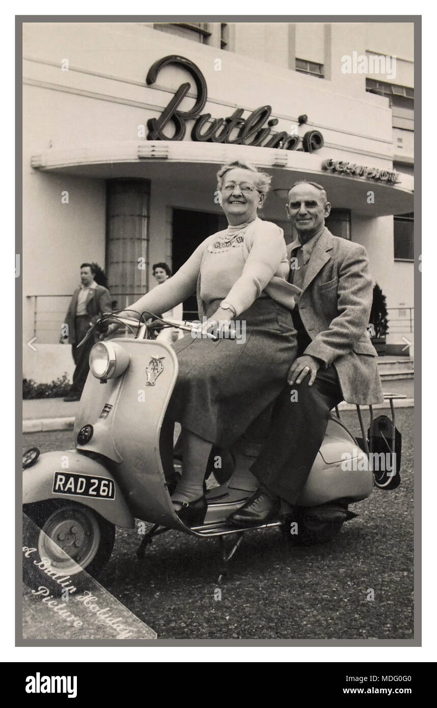 1950's Vintage Butlin's official holiday photograph of a post war happy mature couple astride a (of the era) trendy Lambretta scooter, with the Butlin's Ocean Hotel behind, Saltdean East Sussex UK - Stock Image