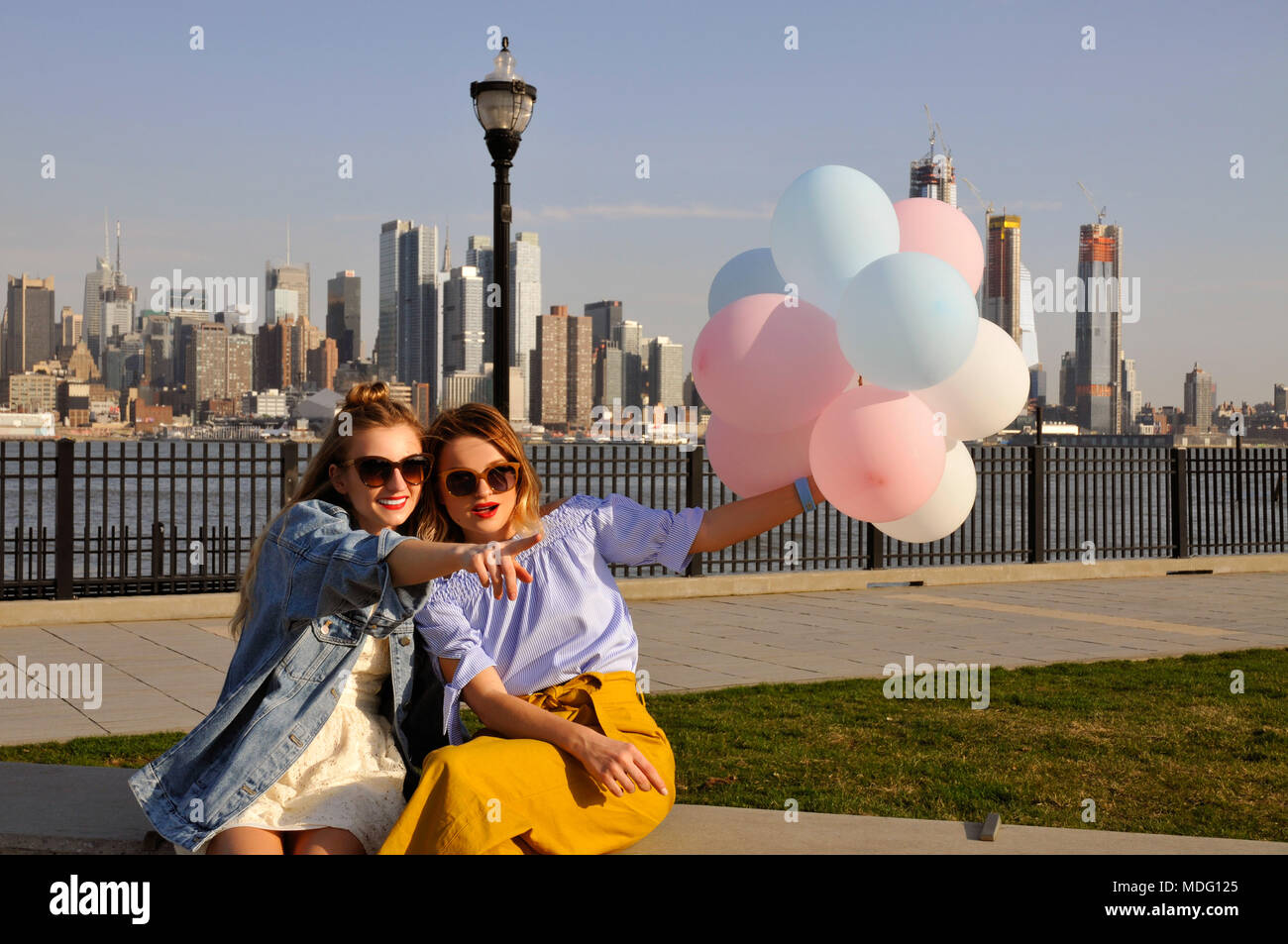 New York city urban women enjoying view of downtown Manhattan skyline. Fashionable girls with balloons, summer travel in USA Stock Photo