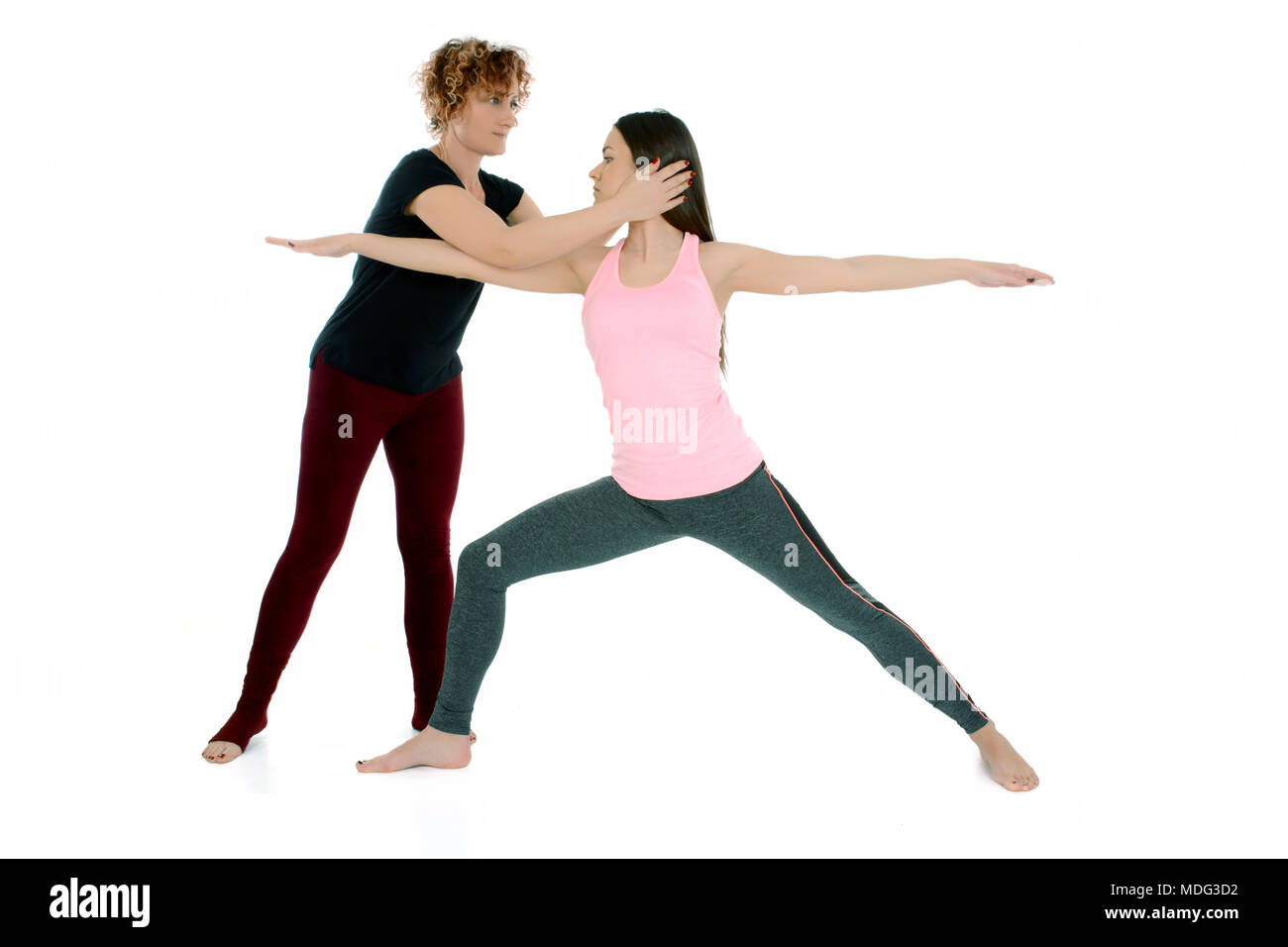 Yoga teacher shows how to put a young white girl in the Yoga position Warrior Pose, on sanskrit Virabradasana. Stock Photo