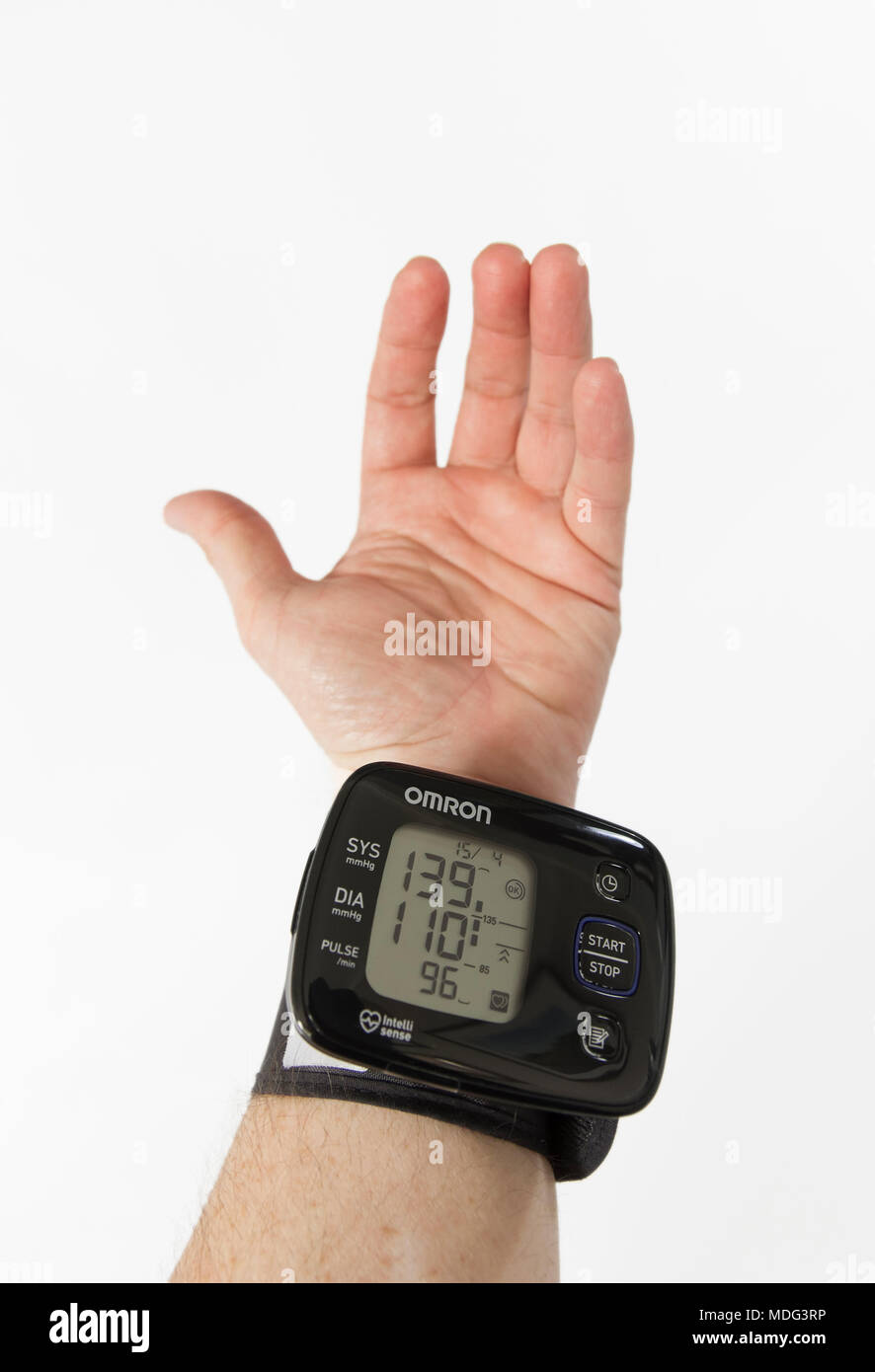 Taking blood pressure readings at home with a wrist monitor. a male hand against a white background - Stock Image