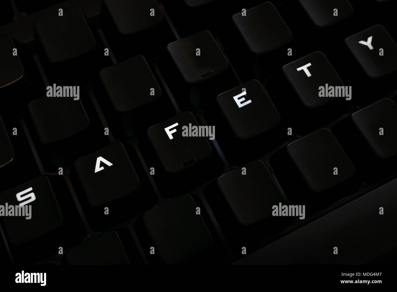 Safety word on keyboard with rearranged letters, backlit keys - Stock Image