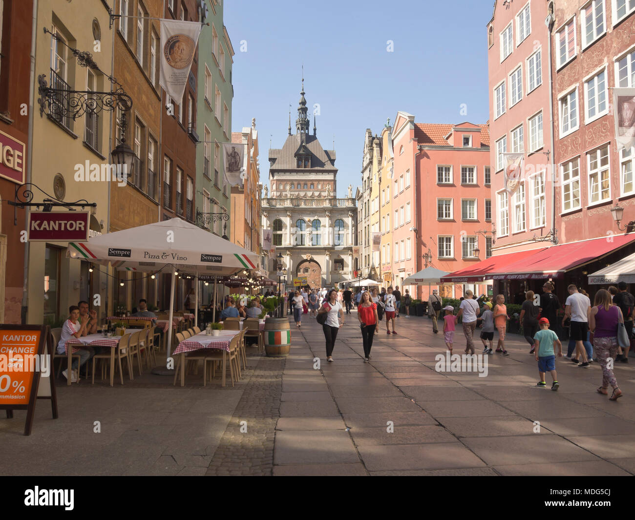 Strolling along in one of the car free streets or visiting an outdoors restaurant in the Main town in Gdansk Poland, are popular tourist activities - Stock Image
