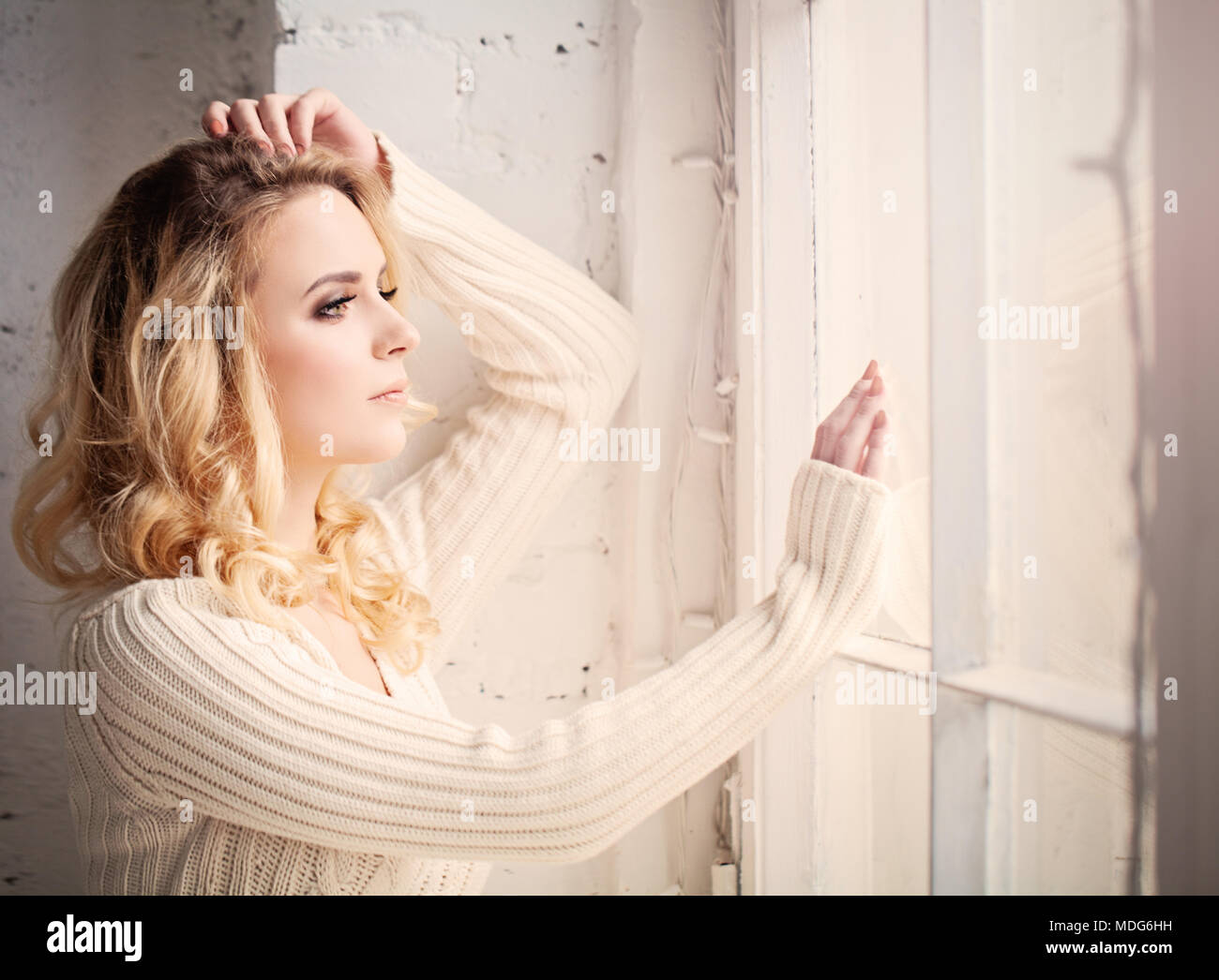 Blonde Woman Looks out the Window and Worries - Stock Image