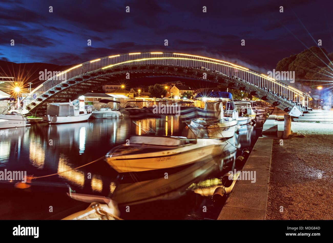 Arched bridge for pedestrians in Trogir, Croatia, Unesco. Night scene. Travel destination. Boats in the port. Yellow photo filter. Stock Photo