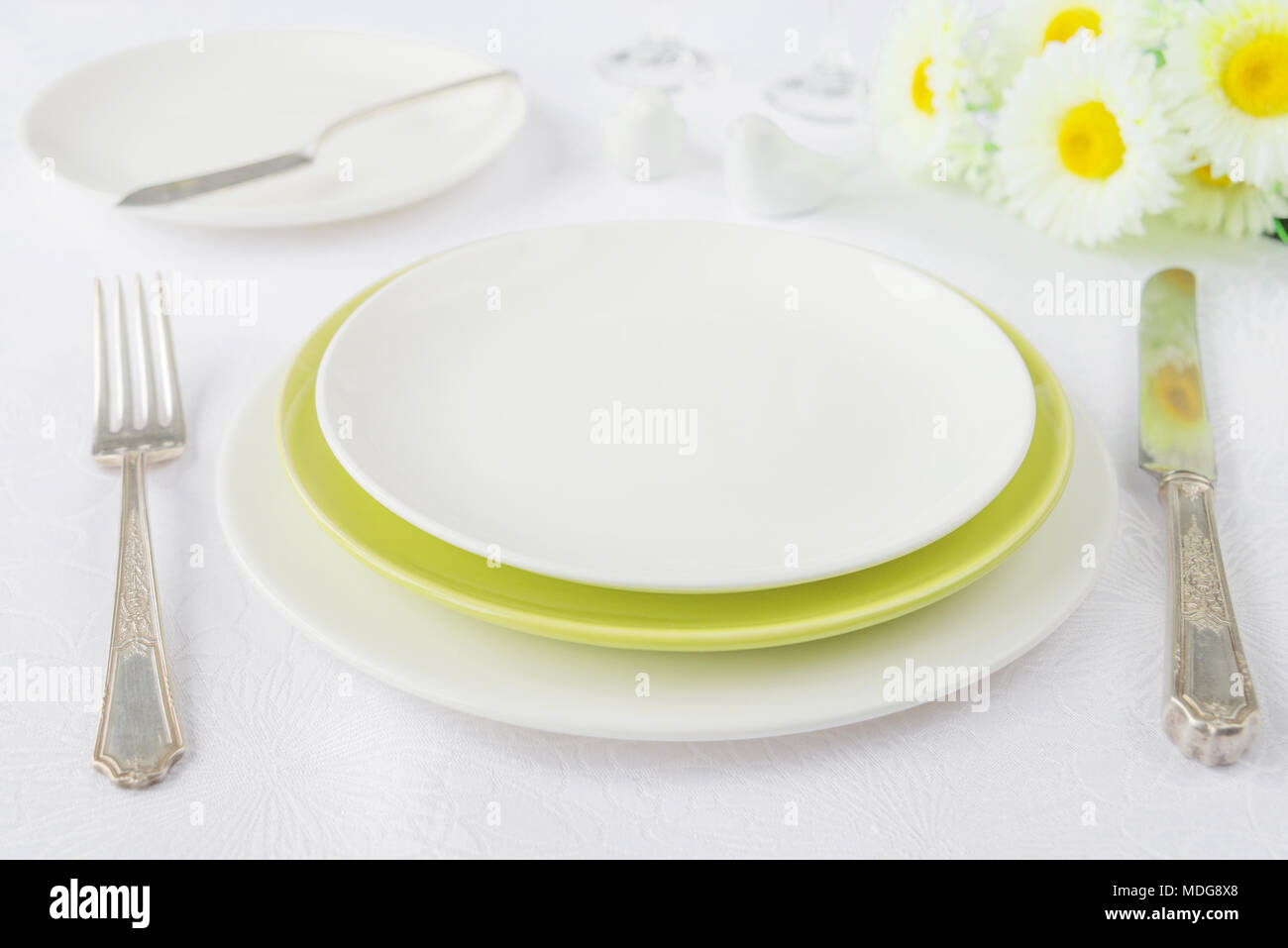 Classic serving for a gala dinner with white and green porcelain plates, silverware and chamomile flowers on a white tablecloth Stock Photo