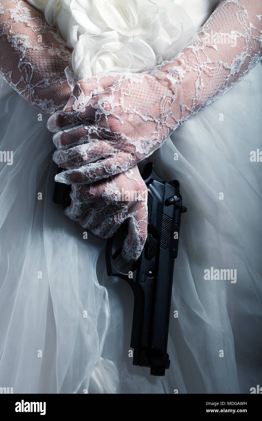 Woman in bridal wear holding a handgun, close up - Stock Image