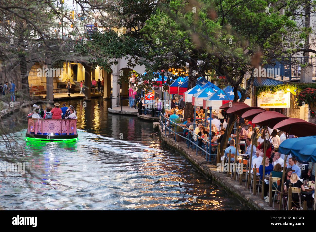 San Antonio River Walk -  - A tourist boat on the San Antonio river passing restaurants at dusk; the San Antonio Riverwalk, San Antonio Texas USA - Stock Image