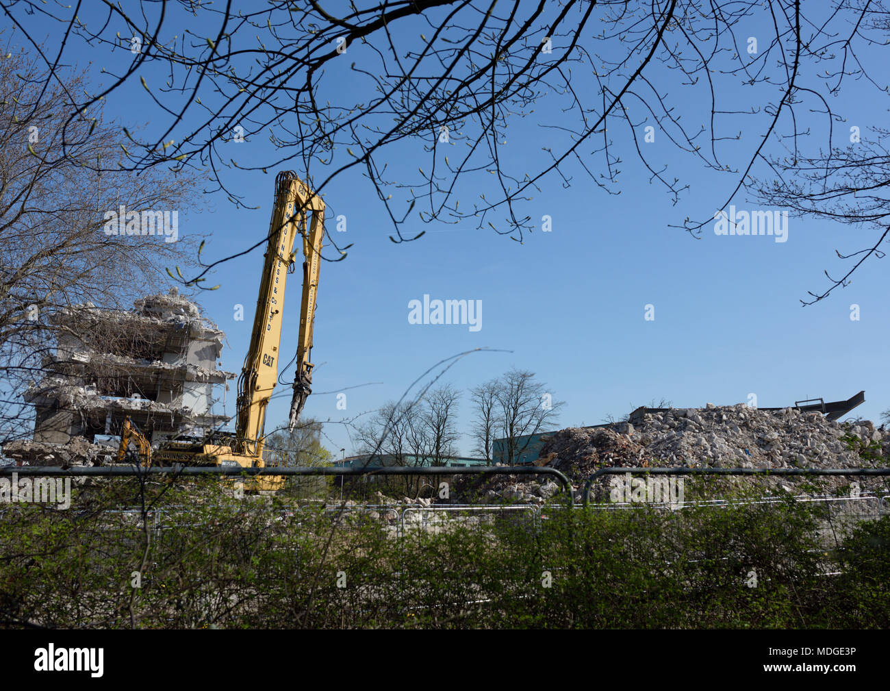 Caterpillar 350 L high reach demolition excavator with concrete crusher attachment  in front of partly demolished concrete building in bury lancashire - Stock Image
