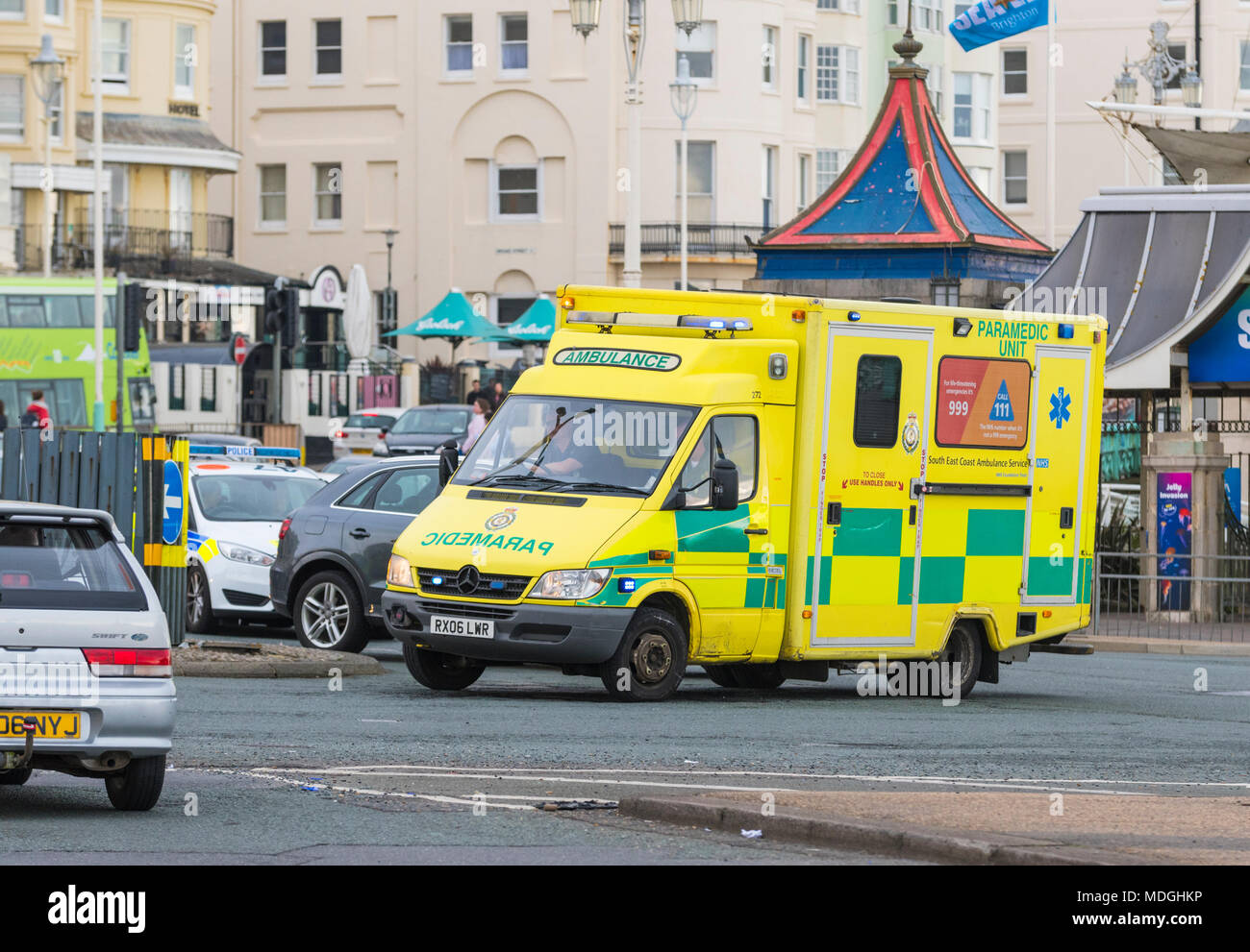 British NHS Ambulance in busy traffic on a roundabout, on a call with blue lights flashing in Brighton, East Sussex, England, UK. Stock Photo