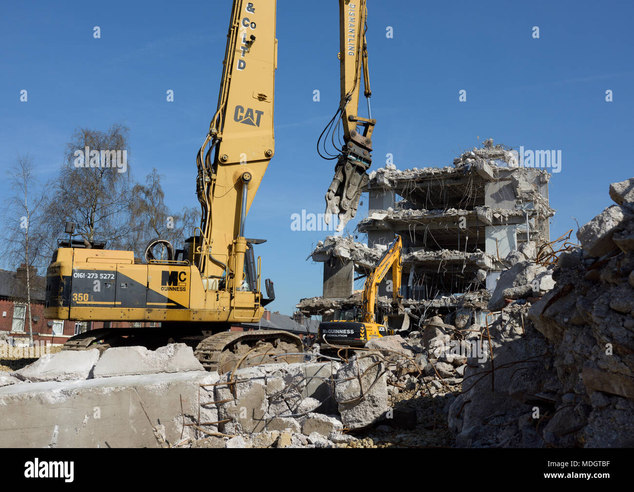 Caterpillar 350L high reach demolition excavator with concrete crusher attachment and concrete rubble in front of partly demolished concrete building - Stock Image