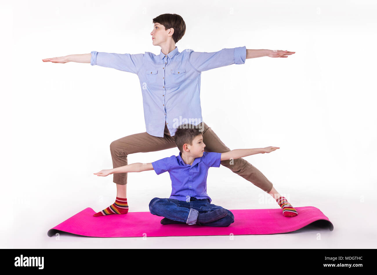 mother and son doing yoga, spending a good time together . isolated on white. Stock Photo