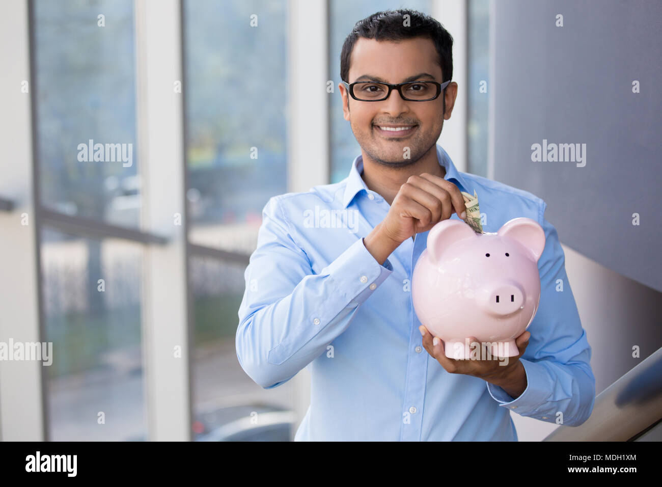 Closeup portrait, young business man in blue shirt, black glasses, putting money in piggy bank, isolated indoor glass background, management and savin - Stock Image