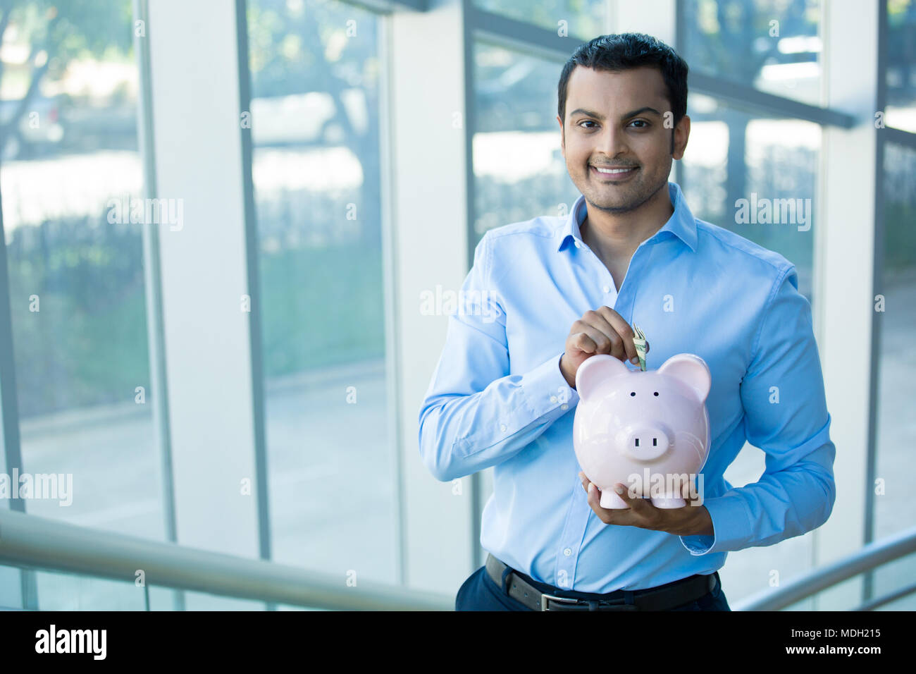 Closeup portrait happy, smiling businessman, placing money in pink piggy bank, isolated indoors office background. Financial budget savings, smart inv - Stock Image