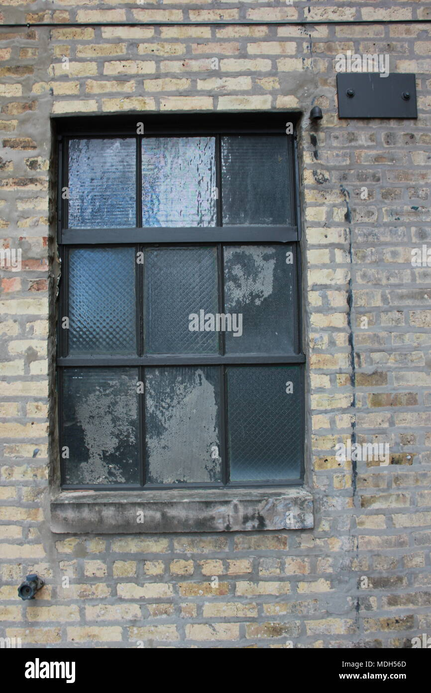 Vintage and weathered glass panel window that is still in use in an alley. - Stock Image