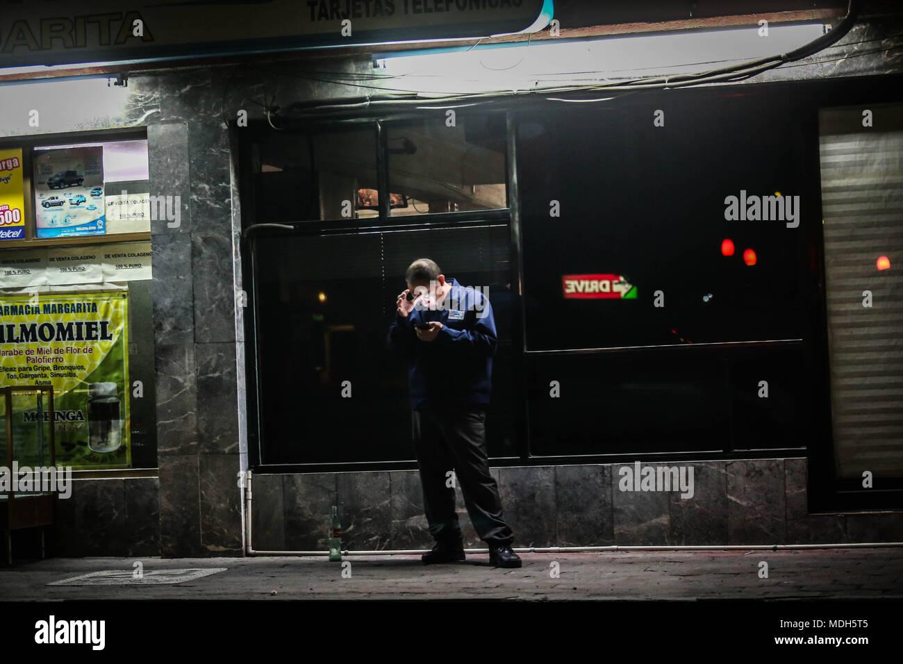 Una persona se detiene al otro lado de la acera de un negocio de cafe para tomar la señal de wifi en su celular. Muchas personas acceden a la red de esta forma - Stock Image
