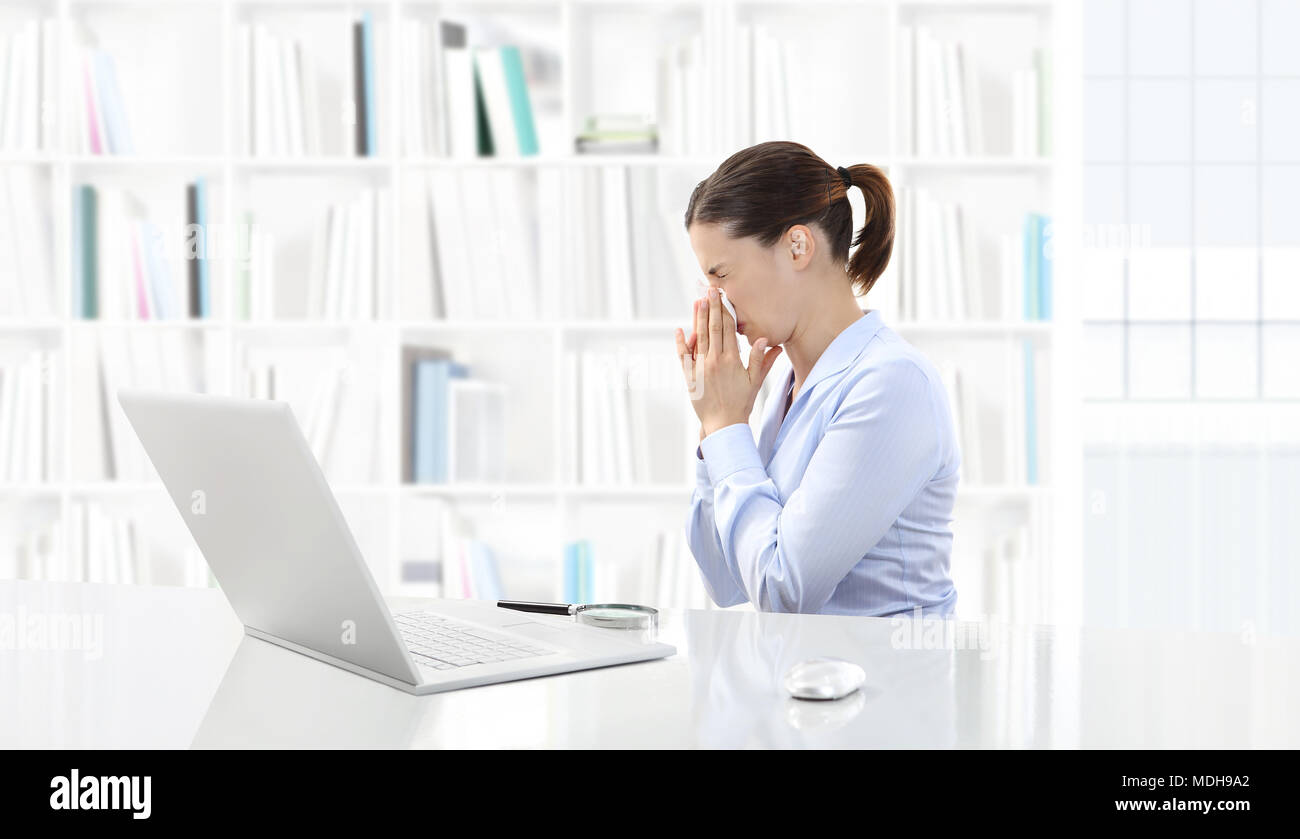 Business woman or a clerk working at her office desk with computer she is sick and sneezes Stock Photo