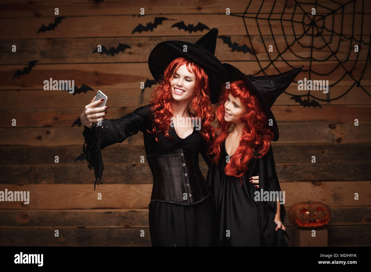 Halloween Concept - Beautiful caucasian mother and her daughter with long red hair in witch costumes taking a selfie with smartphone  ready for celebrating Halloween. Stock Photo