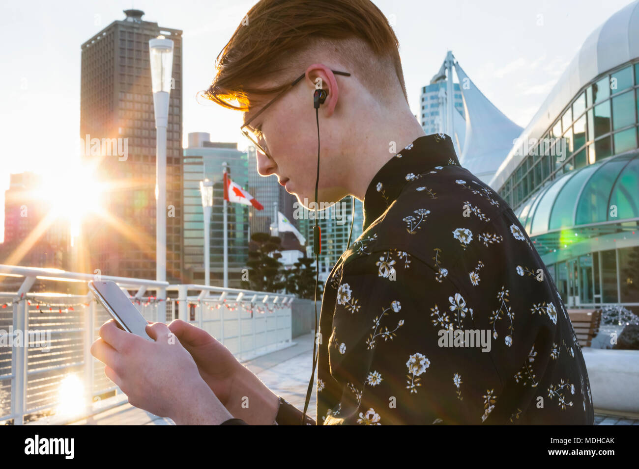 Teenage boy using his smart phone and wearing earbuds in downtown Vancouver; Vancouver, British Columbia, Canada - Stock Image