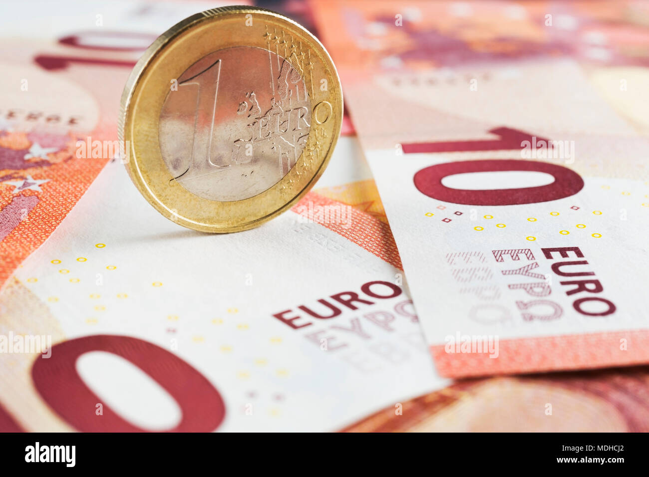 Upright one Euro coin on top of ten Euros denomination paper currency bank notes - Stock Image