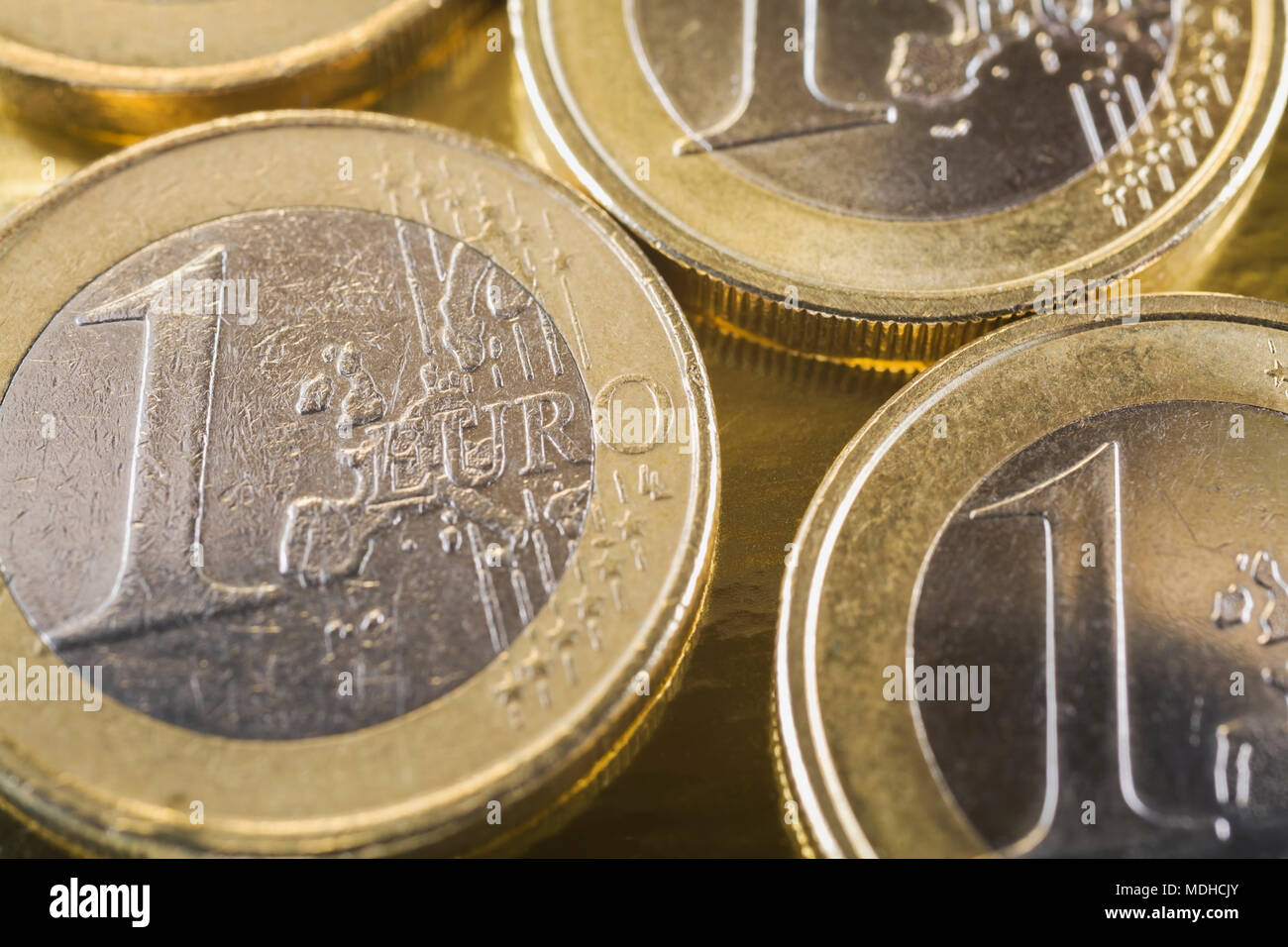 One Euro coins on gold background - Stock Image