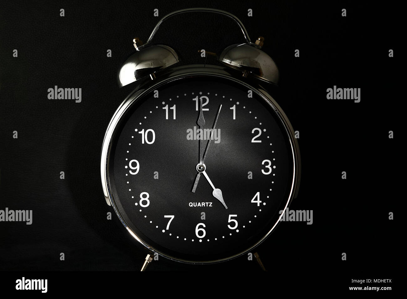 Old retro alarm clock with the hands set to 5:00 am or pm - Stock Image