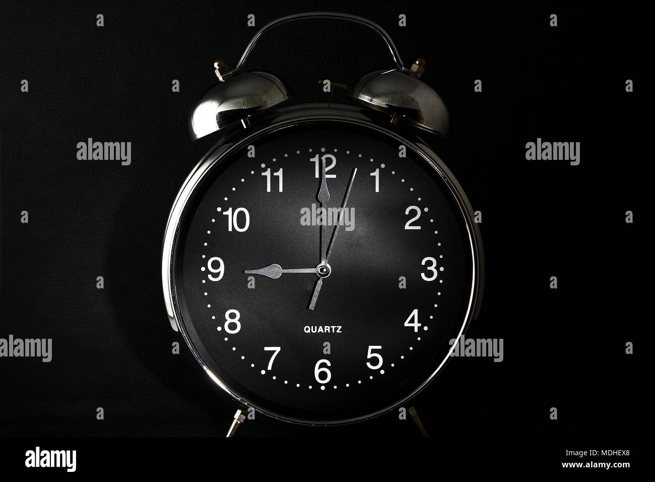 Old retro alarm clock with the hands set to 9:00 am or pm - Stock Image