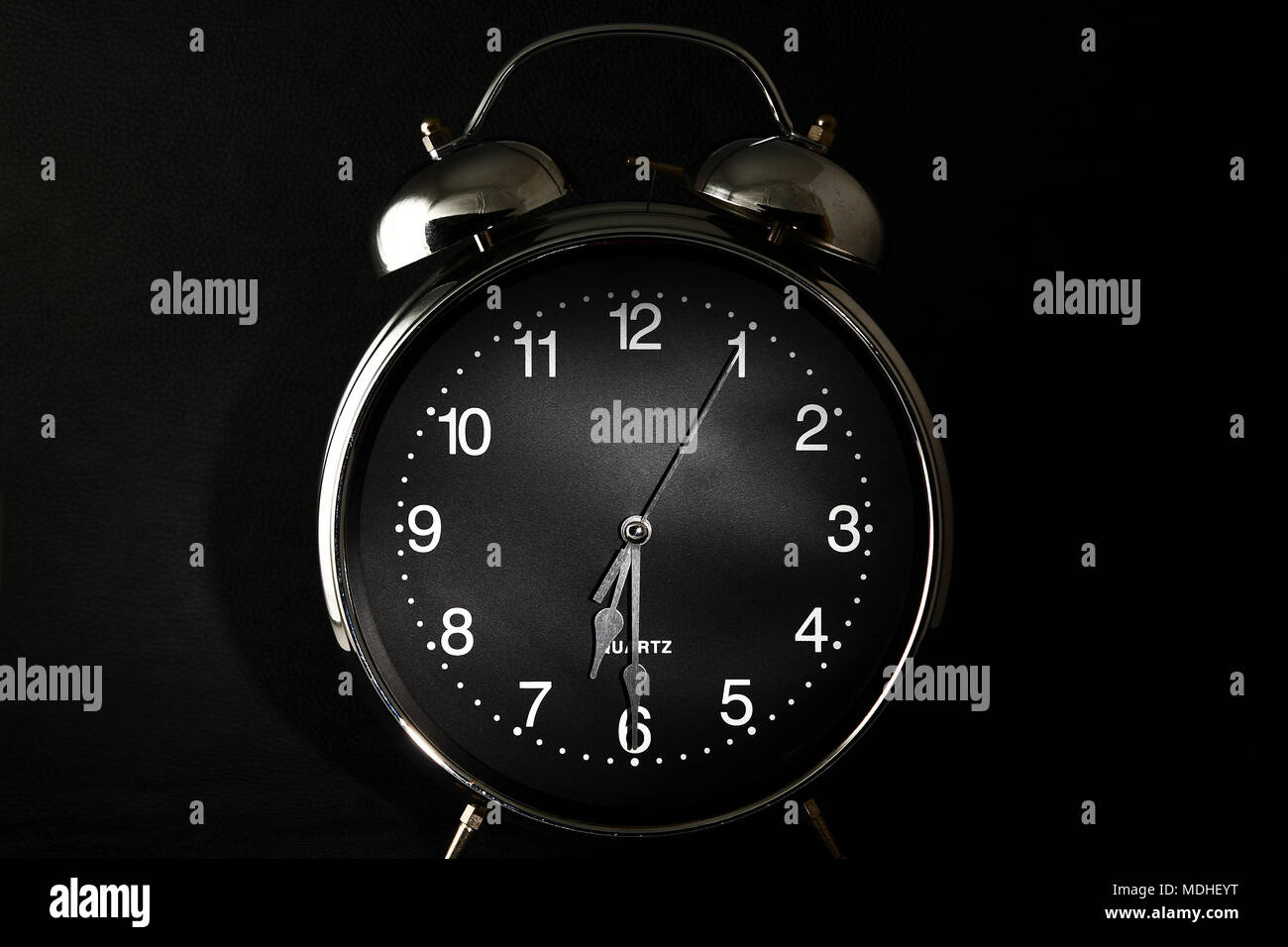 Old retro alarm clock with the hands set to 6:30 am or pm - Stock Image