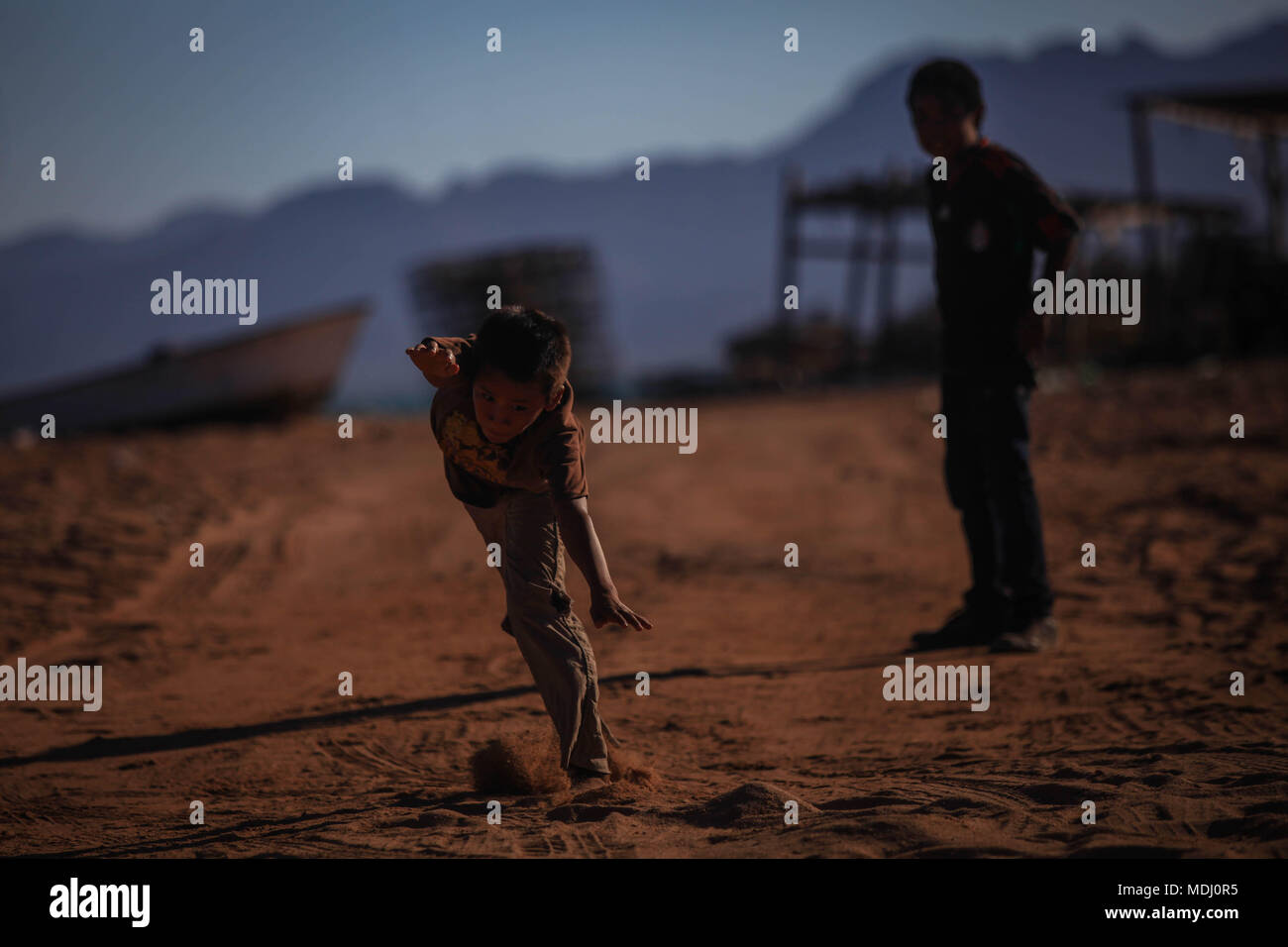 child of indigenous tribe Seri or Conca'ac, Concaac, jumps from a fishing boat or panga and from the ground in the town of Punta Chueca, Sonora. Shark - Stock Image